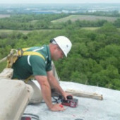 A man performing concrete scanning services at the top of a water tower in Cincinnati Dayton Road in Monroe, Ohio.