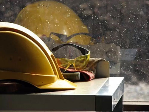 yellow hard hat and yellow goggles on the table by the window